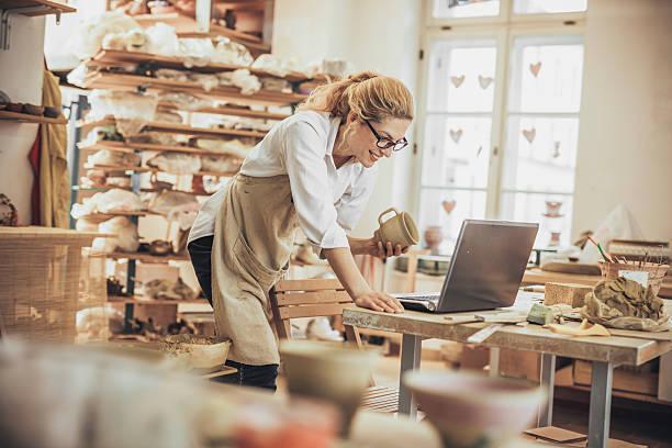 empresário potter usando laptop em oficina - cerâmica artesanato - fotografias e filmes do acervo