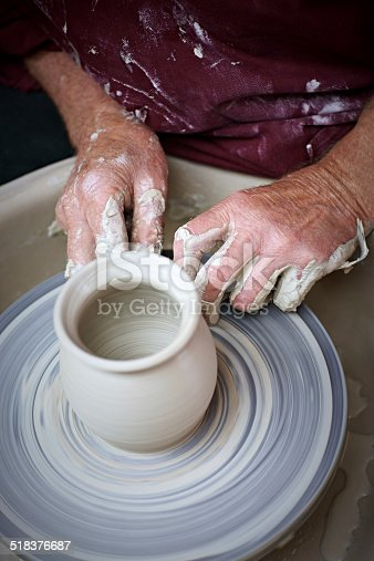 Top view of potter hands making a pot in traditional style on pottery wheel