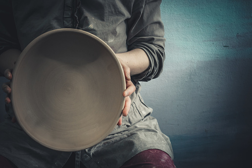Potter holds round clay plate in his hands
