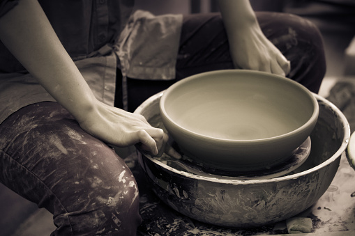 Potter holds round clay plate in his hands.