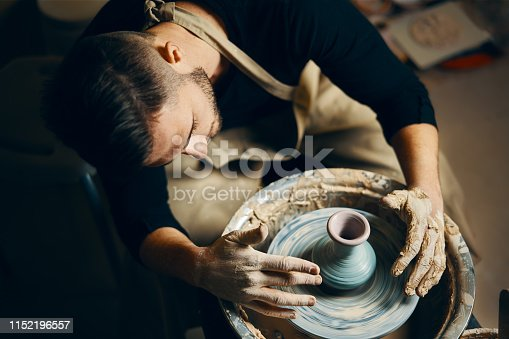 istock Potter modeling ceramic pot from clay on a potter's wheel 1152196557