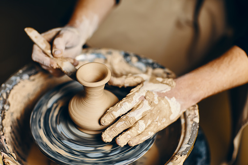 Potter modeling ceramic pot from clay on a potter's wheel