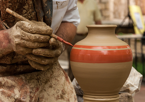 Potter holds a brush to paint a clay vase that rotates on the lathe