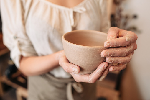 Potter woman keeping clay bowl in dirty palms
