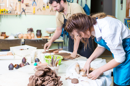 Pottering Concept. Professional Ceramists or Claymakers During a Process of Clay Preparation on Tables in Workshop. Horizontal Composition