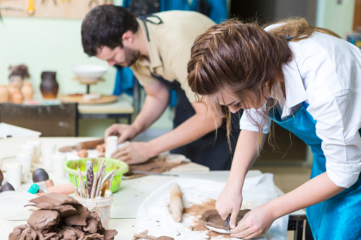 Pottering Concept. Professional Ceramists or Claymakers During a Process of Clay Preparation on Tables in Workshop. Horizontal Shot