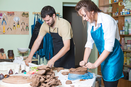 Pottering Concept. Two Professional Ceramists or Claymakers During a Process of Clay Preparation on Tables in Workshop. Horizontal Shot
