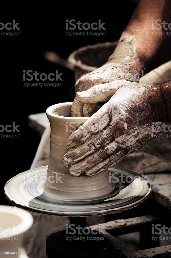 A potters dirty hands turning a beaker on a potter wheel stock photo