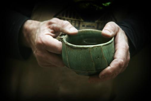 potter's hands hold handmade pottery mug