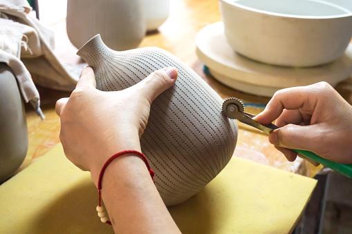 Potter's hands make a decorative pattern on vase