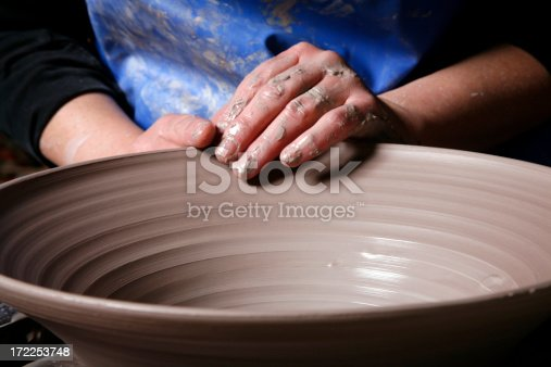 An artisan shapes the rim of a bowl.