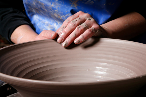 Potters hands shaping rim of clay bowl