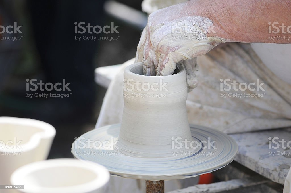 Potters Hands turning a beaker on potter wheel. stock photo