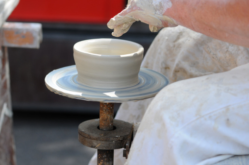 Potters Hands turning a bowl on potter wheel.