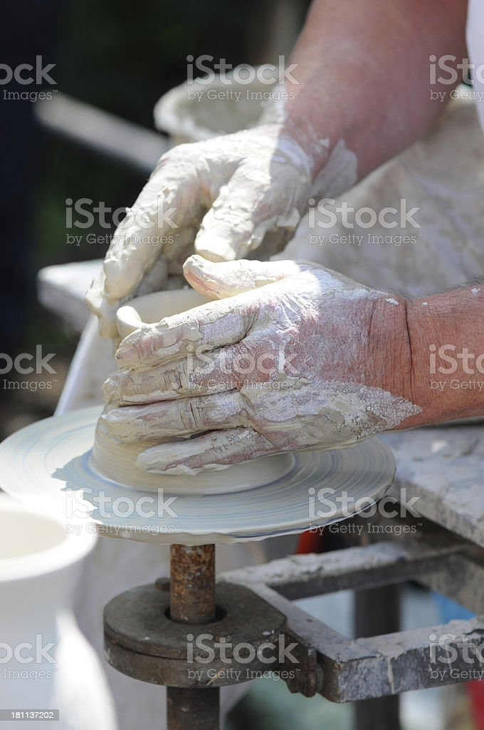 Potters Hands turning a bowl on potter wheel. stock photo