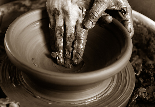 potter's hands with the product on a potter's wheel