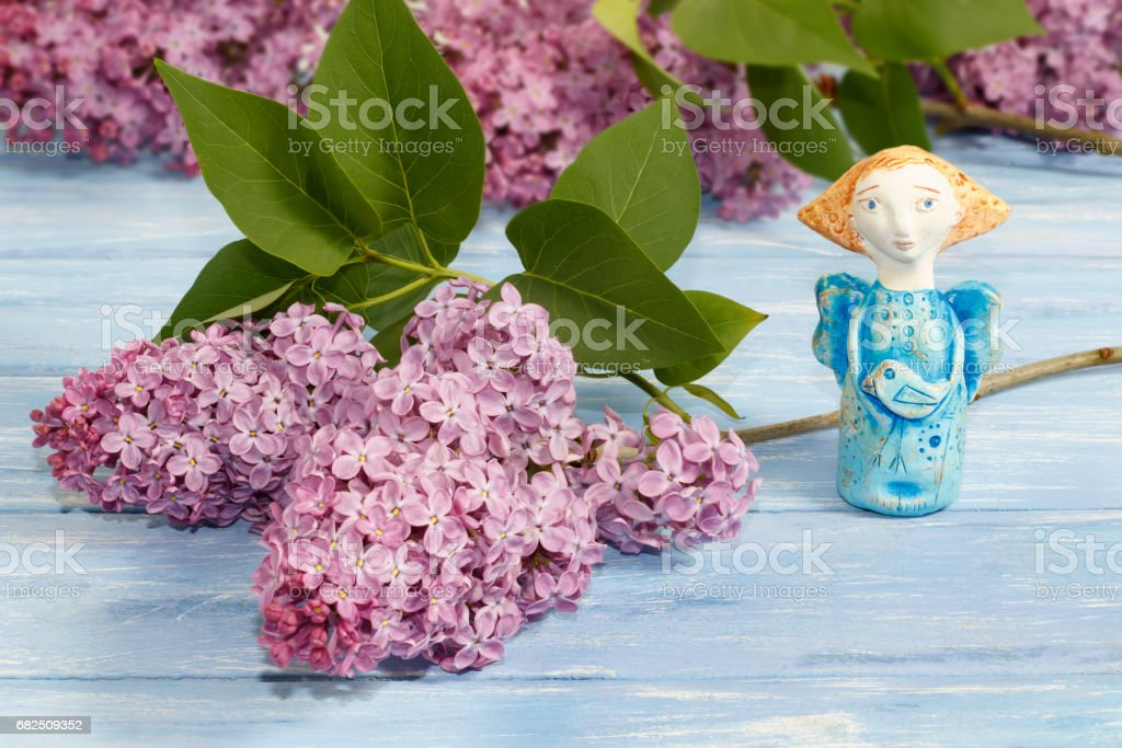pottery angel from clay   and branches of lilac on old blue wooden table royalty-free stock photo