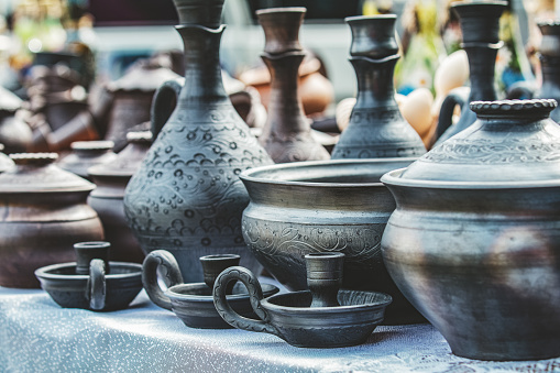 Pottery at Crafts Fair. On a table are beautiful Mugs, Cups and Jugs. On a front side of Mugs, Cups and Jugs are seen a beautiful patterns.