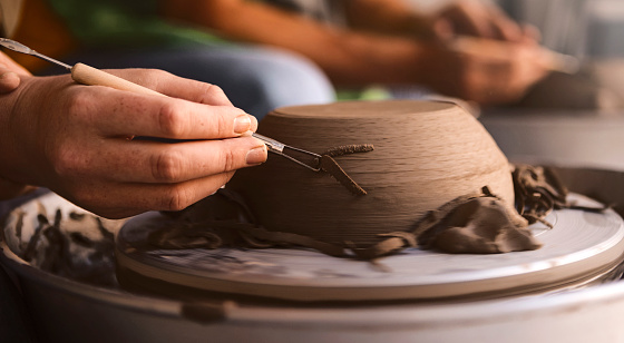 Pottery maker trimming molded clay on a pottery wheel