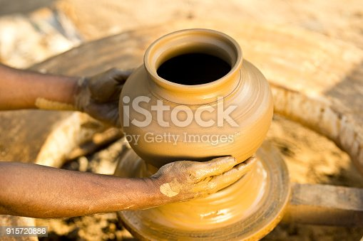 Man forming a clay pot on pottery wheel