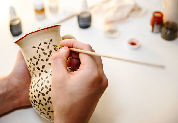 Pottery. Painting pottery. Pottery. Man is painting pottery. craft product stock pictures, royalty-free photos & images