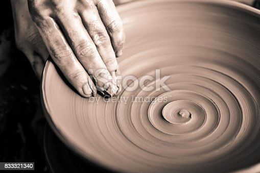 Hand of potter doing  clay pot on background