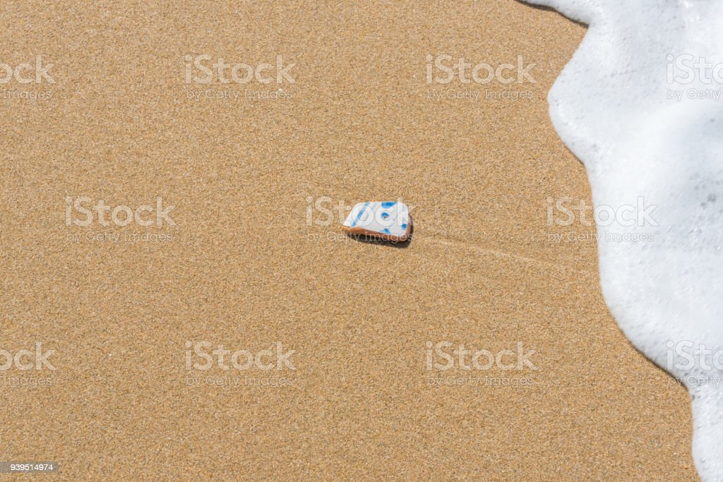 Pottery Shard on a Beach stock photo
