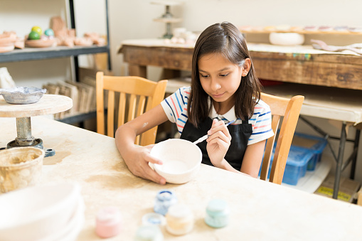 Pottery Student Painting Bowl With Brush At Table
