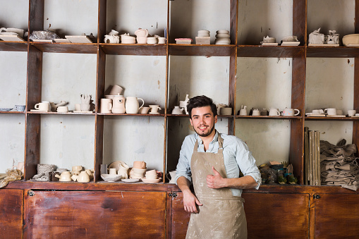 pottery, tools, ceramics art concept - happy handsome young male dressed in an apron stand with finished utensils, smiling ceramist at workplace with baked cups and jugs at background