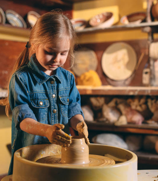 pottery workshop. a little girl makes a vase of clay. clay modeling - teacher school solo imagens e fotografias de stock
