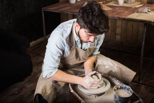 pottery, workshop, ceramics art concept - man working on potter's wheel with raw clay with hands, a male brunette sculpt a utensils near wooden table with tools, master in apron and a shirt, top view stock photo