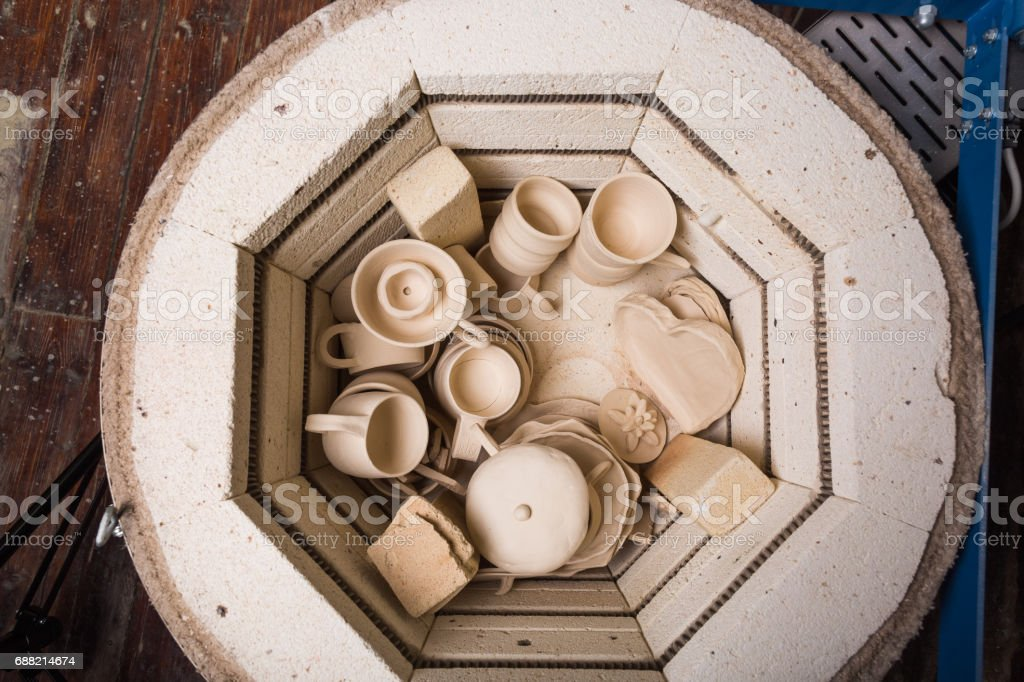 pottery, workshop, ceramics art concept - small electric oven for further roasting of unfinished clay products, kiln for cups and unbaked jugs, flat lay, top view stock photo