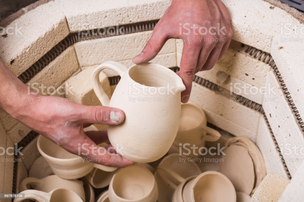 pottery, workshop, ceramics art concept - top view of electric oven for roasting of unbaked clay products, male hands putting the jug in the kiln, some unfinished cups and utensils stock photo