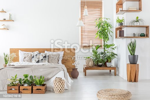 istock Pouf and plants in bright bedroom interior with pillows on bed with wooden headboard. Real photo 1023421616