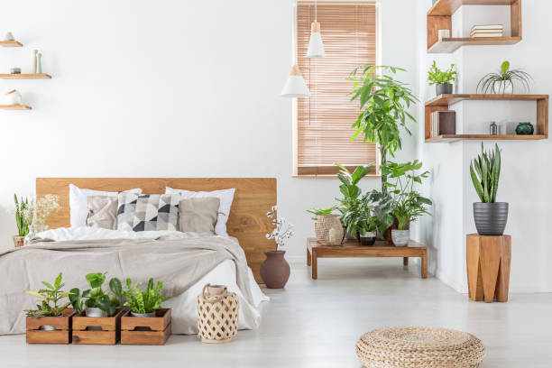 pouf and plants in bright bedroom interior with pillows on bed with wooden headboard. real photo - home decor boho imagens e fotografias de stock
