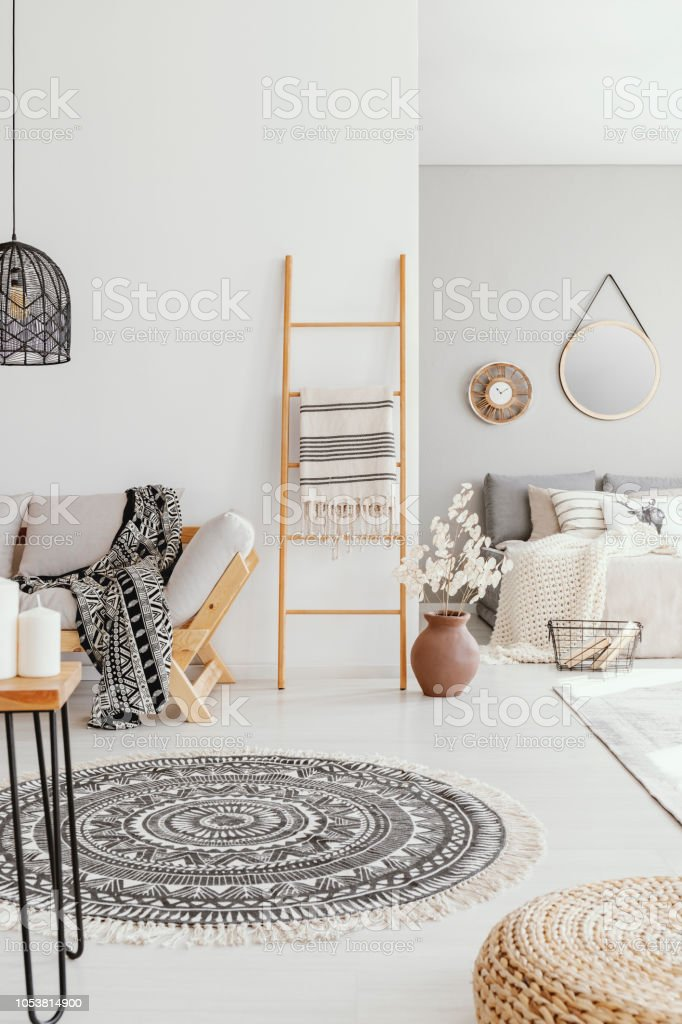 Pouf And Round Rug In Bright Living Room Interior With Ladder Next To  Wooden Couch Real Photo Stock Photo - Download Image Now