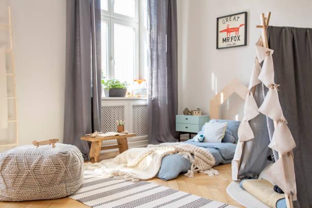 hocker und zelt in skandinavischen schlafzimmer innenraum mit vorhänge am fenster und poster über dem bett. echtes foto - fuchs kissen stock-fotos und bilder