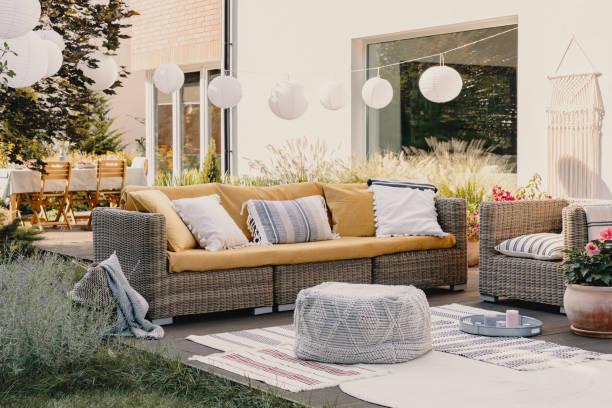 Pouf neben Rattan Couch und Sessel auf Holzterrasse mit Blumen und Lampen – Foto