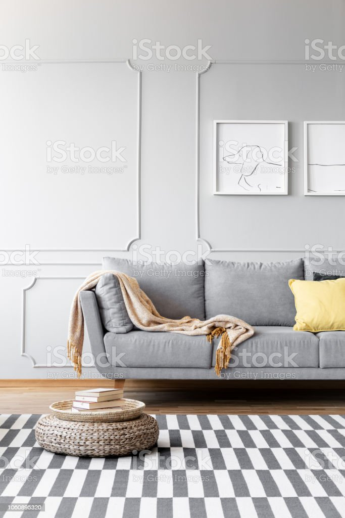 Pouf on carpet in simple living room interior with posters above grey couch  with blanket. Real photo - Stock image . 65ee8adf9