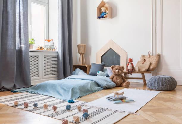 hocker, teppiche und plüschtier in helles kind schlafzimmer innenraum mit fenster und blau bett. echtes foto - fuchs kissen stock-fotos und bilder