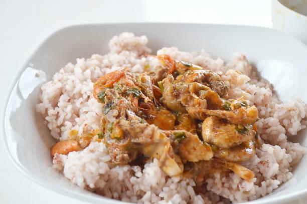 Poulet crevettes sauce coco avec du riz rouge Poulet crevettes sauce coco avec du riz rouge. riz stock pictures, royalty-free photos & images