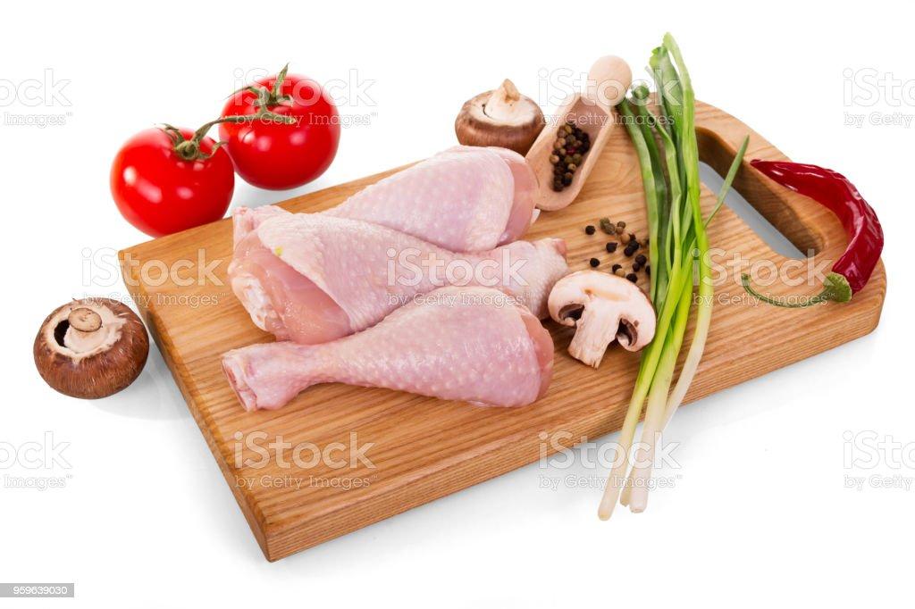 Carne de aves de corral - muslos de pollo y verduras en cortar tablero aislado en blanco - Foto de stock de Agricultura libre de derechos