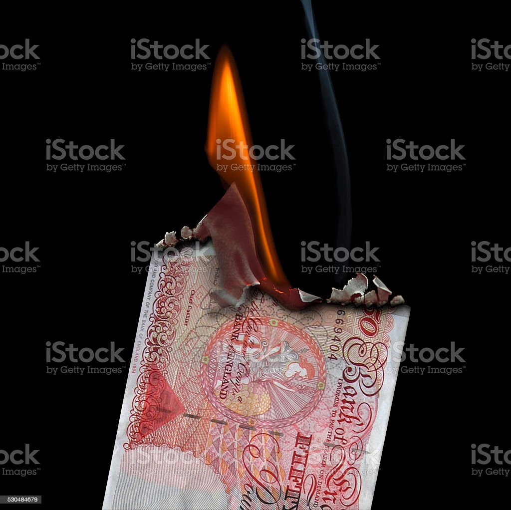 50 Pound Banknote on fire set on a  black background. stock photo