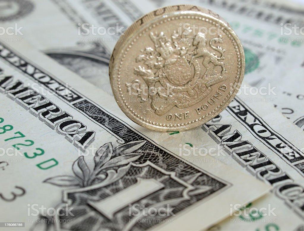 Pound Coin on Dollar Bills stock photo