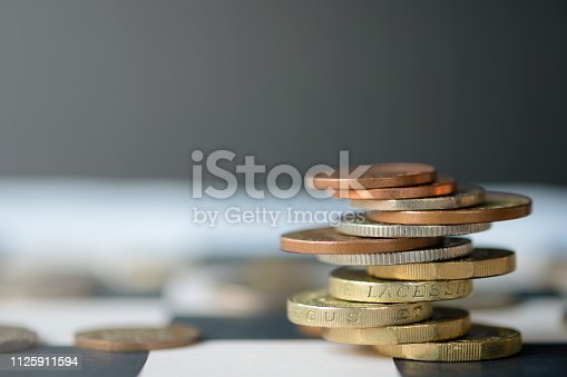 istock Pound sterling coins stacking on chess table with black background.Currency exchange concept.-Image. 1125911594