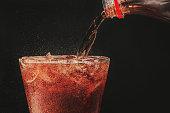 黒い背景にガラスとバブルのソーダにボトルからコーラを注ぐ