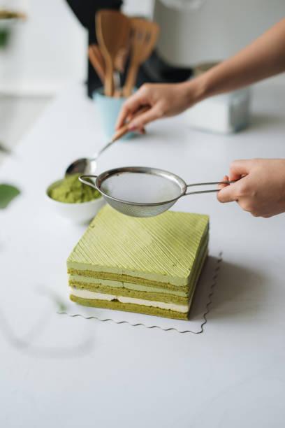 grüntee-pulver über leckere käsekuchen gießen - grüntee kuchen stock-fotos und bilder