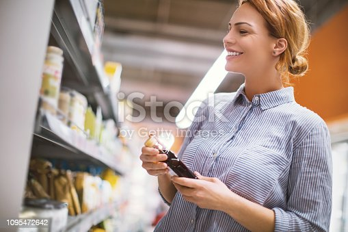 Young woman choosing maple syrup to buy in the supermarket.