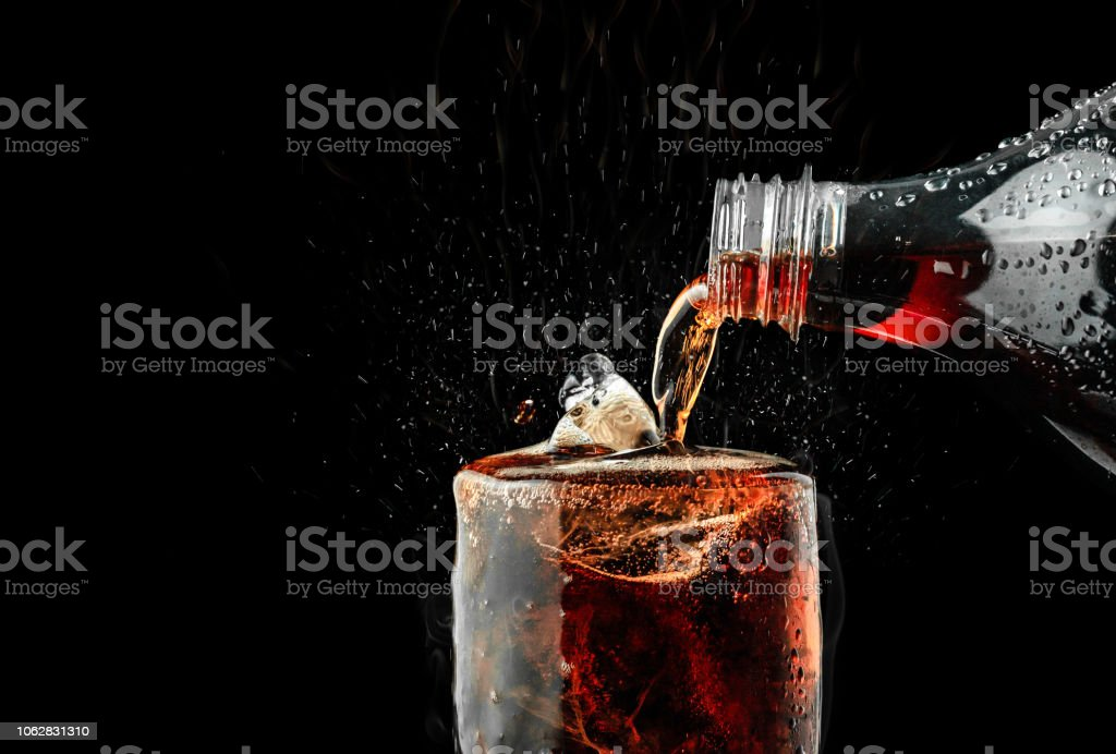 Pour soft drink in glass with ice splash on dark background. royalty-free stock photo