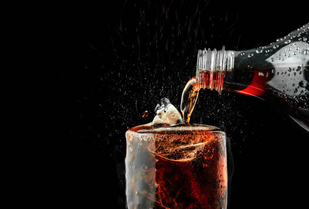 pour soft drink in glass with ice splash on dark background. - bottle soft drink foto e immagini stock